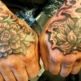 Two hands tattooed with flowers